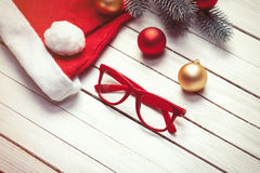 Santas hat and christmas bubbles with red glasses Stock Photography
