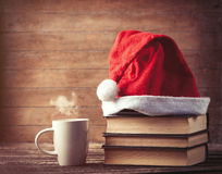 Santas hat over books near hot cup of coffee or tea Stock Image