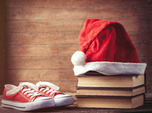 Santas hat over books near red gumshoes Royalty Free Stock Image