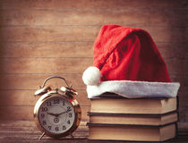 Santas hat over books near retro alarm clock Royalty Free Stock Images
