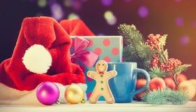 Santas hatt och pepparkaka med koppen Arkivfoto