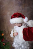 With Santas Help. Toddler getting helped by santa, dressing up like santa royalty free stock photo