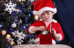 Santas Helper. Little Elf Helping Santa box gifts stock image