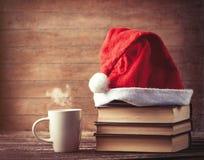 Santas kapeluszowe nadmierne książki zbliżają gorącą filiżankę kawy lub herbaty Obraz Stock