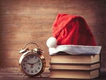 Santas kapeluszowe nadmierne książki zbliżają retro budzika Obrazy Royalty Free