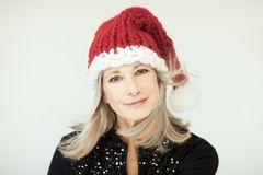 Santas little helper. Beautiful happy senior woman with a santa claus hat Royalty Free Stock Image