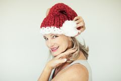 Santas little helper. Beautiful happy senior woman with a santa claus hat Stock Images
