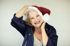 Santas little helper. Beautiful happy senior woman with a santa claus hat, and winter jacket Stock Photos