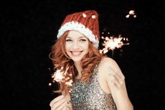 Santas little helper. Beautiful happy young woman with a santa claus hat, perfect make up, red lipstick, holding sparkler lights royalty free stock photos