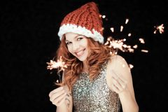 Santas little helper. Beautiful happy young woman with a santa claus hat, perfect make up, red lipstick, holding sparkler lights royalty free stock images