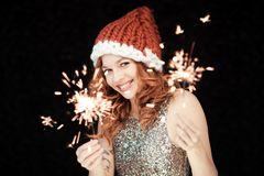 Santas little helper. Beautiful happy young woman with a santa claus hat, perfect make up, red lipstick, holding sparkler lights stock photos