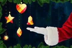 Santas räcker att låtsa som rymmer en julklocka mot digitalt frambragd bakgrund Arkivfoto