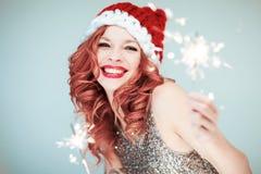 Santas Weinig Helper De mooie gelukkige jonge vrouw met een hoed van de Kerstman, perfectioneert omhoog maakt, rode lippenstift royalty-vrije stock foto's