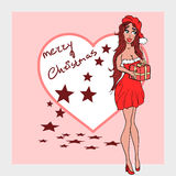 Santas wife in a red dress wishing you a merry christmas Stock Photo