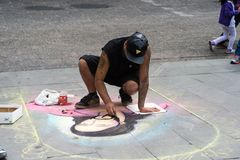 People of Chile. SANTIAGO, CHILE - NOV 1, 2014:  Unidentified Chilean man draws a Jesus Christ image on the ground in Santiago. Chilean people are mainly of Royalty Free Stock Image