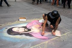 People of Chile. SANTIAGO, CHILE - NOV 1, 2014:  Unidentified Chilean man draws a Jesus Christ image on the ground in Santiago. Chilean people are mainly of Stock Photos