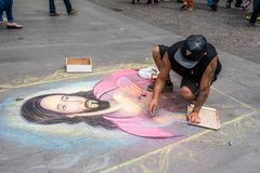People of Chile. SANTIAGO, CHILE - NOV 1, 2014:  Unidentified Chilean man draws a Jesus Christ image on the ground in Santiago. Chilean people are mainly of Stock Images