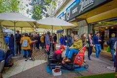 SANTIAGO, CHILE - 16. OKTOBER 2018: Ansicht im Freien der Menge der Leute, die in den Bürgersteig nah an einem Mann sitzt in a ge stockfotografie