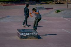 SANTIAGO, CHILE - SEPTEMBER 13, 2018: Outdoor view of two young teenagers skating and umping in a public stoned park Royalty Free Stock Photography