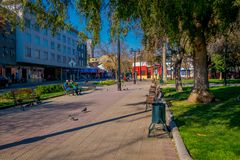 SANTIAGO, CHILE - SEPTEMBER 13, 2018: Unidentified people sitting in a public wooden chair relaxing at Yungay park. Located in the Barrio Yungay in Santiago Royalty Free Stock Photo