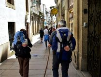 Pilgrims with scallop shell, symbol of camino de Santiago, walking in old town. Santiago de Compostela, Spain, 5 May 2019. royalty free stock photos