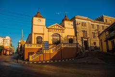 Santiago de Cuba, Cuba: Sala dolortes, Yellow building with turrets and clock on the street. Santiago de Cuba, Cuba: Sala dolortes, Yellow building with turrets Royalty Free Stock Photography