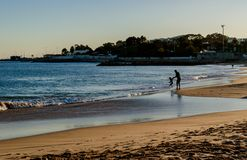 Santo Amaro de Oeiras - March 10, 2019 - Portuguese coastline, silhouettes of father and son playing near the sea on the beach royalty free stock photography