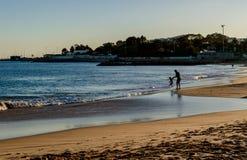 Santo Amaro de Oeiras - mars 10, 2019 - portugisisk kustlinje, konturer av fadern och son som spelar nära havet på stranden royaltyfri fotografi
