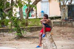 SANTO DOMINGO, ΔΟΜΙΝΙΚΑΝΉ ΔΗΜΟΚΡΑΤΊΑ - 8 ΑΥΓΟΎΣΤΟΥ 2017: Ένας μαύρος τύπος κάθεται σε μια οδό πόλεων Διάστημα αντιγράφων για το κ Στοκ Φωτογραφία