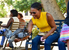 Santo Domingo, Dominican Republic. Woman feeds pigeons on Columbus Park, Colonial Zone of Santo Domingo. Santo Domingo, Dominican Republic. Woman feeds pigeons Royalty Free Stock Images