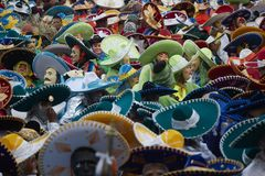 Crowd of masked people wearing colorful charros hats at mexican carnival stock photos
