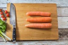 Santoku kuchenny nóż na tnącej desce z świeżymi warzywami: marchewki, pomidory, sałata i zielona cebula na drewnianym tle, Fotografia Royalty Free