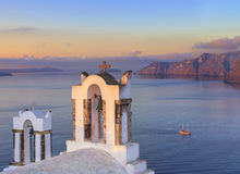 Santori belltowers facing the volcano. Santori belltowers at sunset facing the volcano in the sea Stock Images