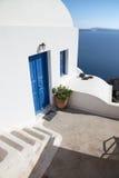 Santorini - κοιτάξτε για να στεγάσετε χαρακτηριστικά ower caldera με τα άσπρα σκαλοπάτια και τα μπλε dors Oia Στοκ Εικόνες