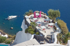 Santorini - το εστιατόριο που συνδέονται με το γαμήλιο ρομαντικό γευματίζοντα Oia (Ia) και το γιοτ κάτω από τους απότομους βράχου Στοκ Φωτογραφίες