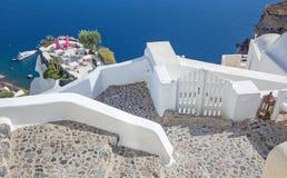 Santorini - το εστιατόριο που συνδέονται με το γαμήλιο ρομαντικό γευματίζοντα Oia (Ia) και το γιοτ κάτω από τους απότομους βράχου Στοκ Εικόνες