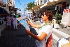 Santorini, Греция, 21-ое сентября 2018, турист смотрит карту стоковое фото rf