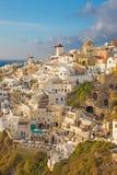 Santorini - blicken till delen av Oia med väderkvarnarna i aftonljus Royaltyfri Bild