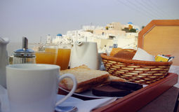 Santorini breakfast scene. Tasty breakfast served on the balcony with the view on Greek village Royalty Free Stock Photos