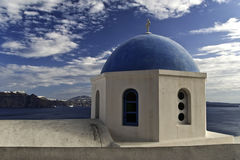 Santorini Church Against Cloudy Sky. The dome of a Greek Orthodox church in Santorini, Greece, is silhouetted against a cloudy afternoon sky Royalty Free Stock Images