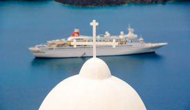 Santorini church cross and cruise ship Stock Photos