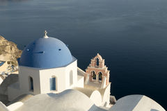 Santorini church dome. The blue dome of a church in Oia village, Santorini with the blue water of the caldera in the background Stock Images