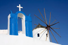 Santorini, A church and a Windmill. Picture taken in Santorini, Greece. Blue and white buildings Stock Photos