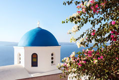 Santorini classic blue dome church. Greece. Santorini, classic view of blue dome church with Bugambilia Flowers. Oia Village, Greece stock photos
