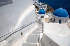 Santorini, Creta, Grecia: una scala e una parete bianche conduce alla chiesa ortodossa Cupola blu della chiesa contro fotografia stock