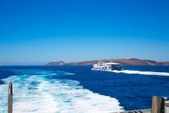 Santorini, Crete: Biali Ferryboat seajets pÅ'ywajÄ… statkiem na tÅ'o wyspie Santorini w Crete w morzu zdjęcie stock