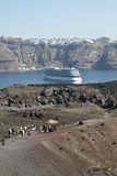 Santorini cruise ship. A group of tourists on the volcanic island Nea Kameni with a cruise ship in the caldera and Thira in the background Royalty Free Stock Image