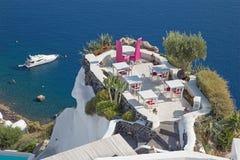 Santorini - das Restaurant übersetzt zur Heirat des romantischen Restaurants in Oia (Ia) und der Yacht unter Klippen Stockfotos