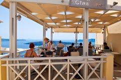 SANTORINI, FIRA- 28 DE JULIO: Restaurante local con la opinión en julio 28,2014 del volcán en la ciudad de Fira en la isla de San Fotografía de archivo libre de regalías