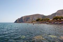 SANTORINI, FIRA- 28. JULI: Touristen nehmen auf dem Kamari-Strand 28,2014 im Juli ein Sonnenbad Santorini (Thira), Griechenland Stockfotos